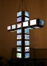 Wojtek Ulrich. Untitled (48 Channel Cross). 48 LED monitors, DVD players, satellite dish with live video feed. 2004